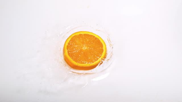 Orange, citrus sinensis, Slice Falling on Water and splashing, against White Background, Slow Motion 4K video