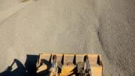 Orange excavator bucket scoops up crushed stone, view of top video