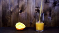 Orange Juice is Poured into a Glass on a Wooden Background. Slow Motion video