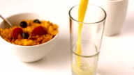 Orange juice pouring into glass at breakfast table video