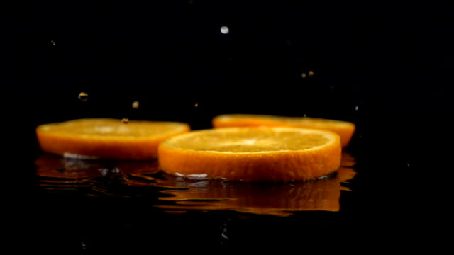 orange slices fall on the black surface covered with water video
