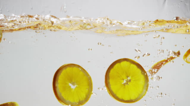 Orange slices falling into water video