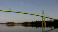 Orange truck crosses green bridge. video