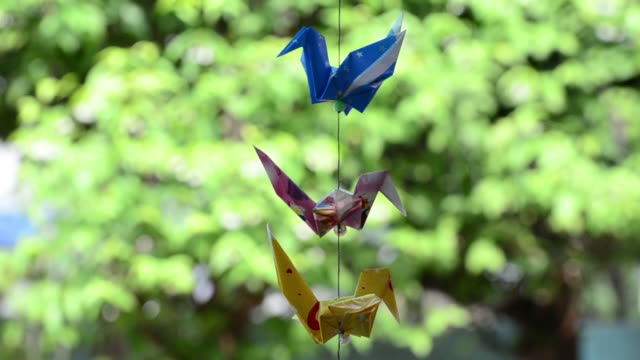 Origami crane playing on bokeh background video