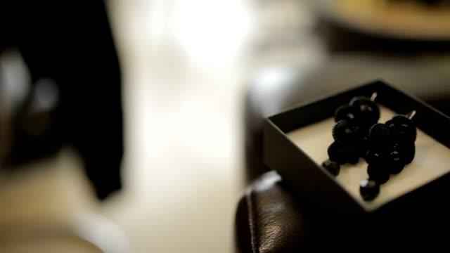 MEDIUM SHOT PANNING Ornate black earrings in box on leather sofa video