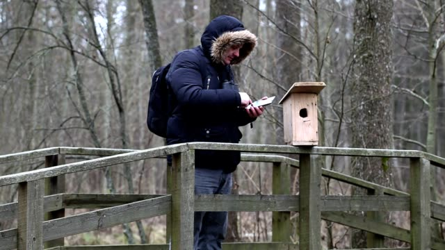 Ornithologist using tablet PC near bird cage video