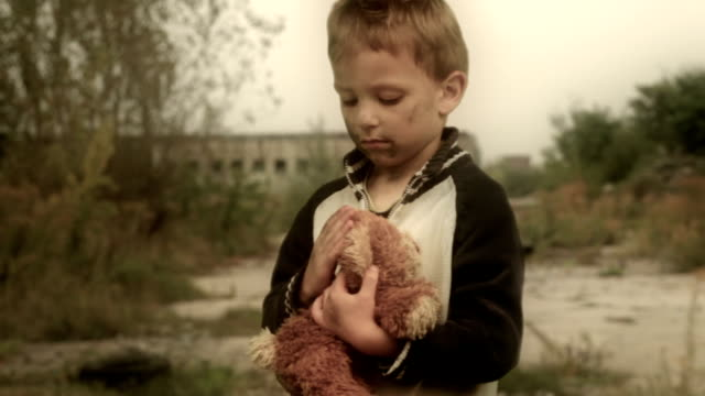 Orphan. Abandoned, lonely child. Ruins in the background. video
