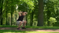 Outdoor fitness. Fitness man workout at park. Man doing squats. Fit man crouch video
