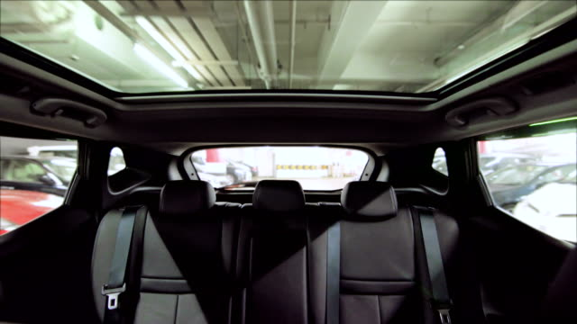 Outdoor glass roof top car cabin. Driving in indoor carpark. video