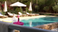 Outdoor swimming pool and garden with sun loungers, shot on R3D video