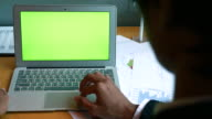 Over shoulder shot of Businessman using laptop with a green screen, 4k(UHD) video