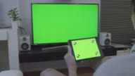 Over shoulder shot of digital tablet and TV,Green screen video