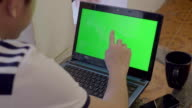 Over shoulder shot of laptop with a green screen video