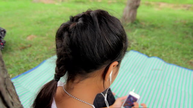 Over the shoulder footage with Girl palying Smart Phone video