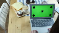 Over the Shoulder view of Woman Using Laptop with Green screen with Breakfast, Chroma key video
