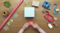 Overhead aerial footage of woman making ribbon flower for gift video