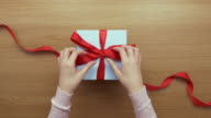 Overhead aerial footage of woman opening red ribbon on gift video