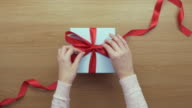 Overhead aerial footage of woman opening ribbon on empty gift video