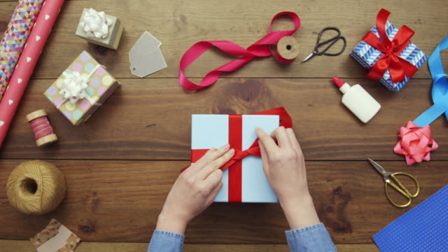 Overhead aerial footage of woman tying red ribbon on gift video