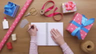Overhead aerial footage of woman with diary wrapping presents video