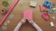 Overhead aerial footage of woman wrapping gift with pink paper video