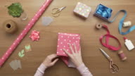 Overhead aerial footage of woman wrapping present box with paper video