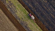 Overhead aerial of a tractor plowing a field video
