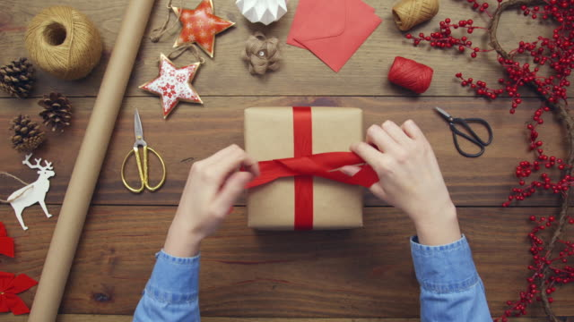 Overhead aerial of woman tying red ribbon on Christmas gift video