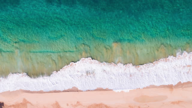 Overhead Aerial View Of Ocean Waves Crashing On Tropical Beach video