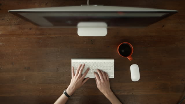 Overhead desk with desktop computer and hands typing video