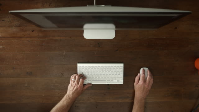 Overhead desk with desktop computer and male hands typing video