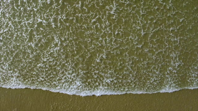Overhead drone footage of sea waves reaching shore video