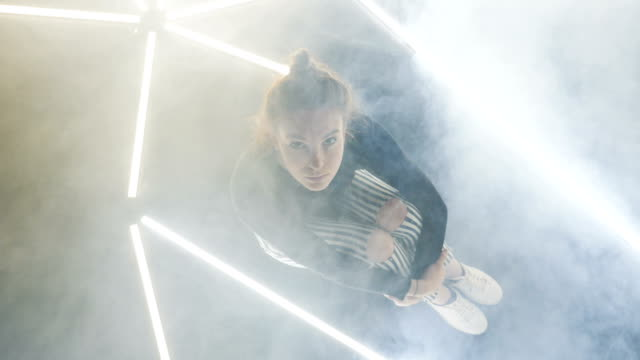 Overhead of a Female Dancer Sitting on the Smokey Dance Floor video
