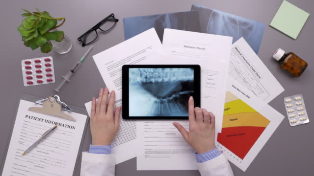 Overhead Of Doctor Examining Reports On Digital Tablet video