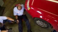 Overhead shot of auto mechanics working in shop video