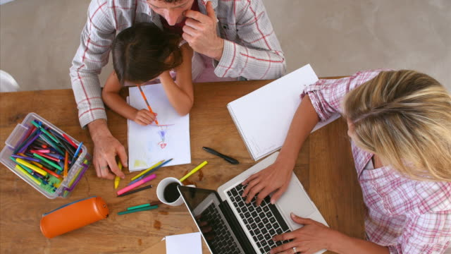 Overhead View Of Family Coloring Picture And Using Laptop video
