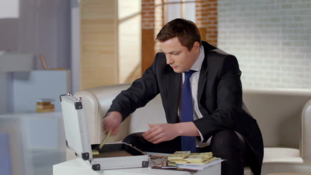 Overjoyed businessman grabs money from briefcase, success, greed video