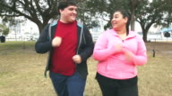 Overweight Hispanic couple having fun exercising video