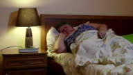Overweight older woman lying in bed talking on phone at night video