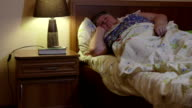 Overweight senior woman in bed at home talking on phone video