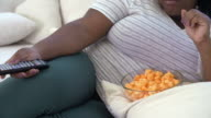 Overweight Woman At Home Eating Snacks And Watching TV video