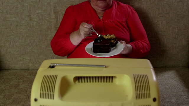 Overweight woman eating cake and watching vintage TV video
