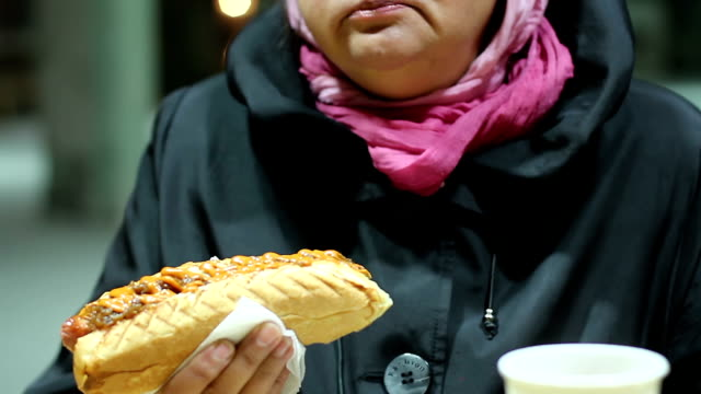 Overweight woman eating greasy hot dog at street snack bar, video