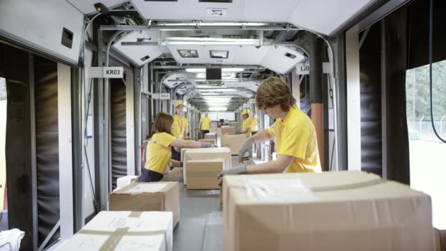 POV Package travelling on the conveyor belt and the postal workers are sorting the surrounding packages video