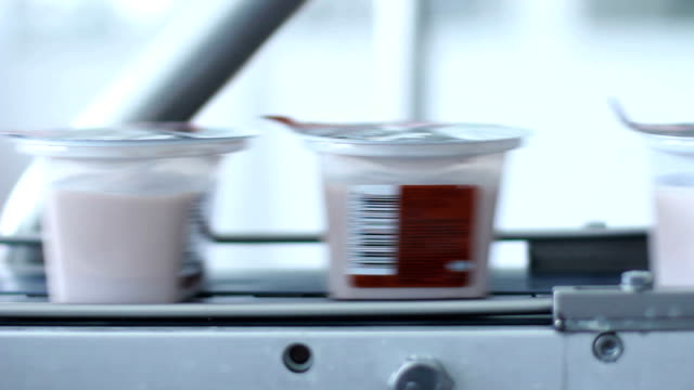 Packaged food on conveyor belt at food factory. Dairy product in plastic container on production line at dairy plant. Yogurt in pack on a conveyor belt. Plastic package on manufacturing line video