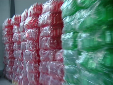 packaged red and green pet bottles in warehouse. video