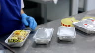 Packaging aluminum containers with food and labeling in factory of flight catering video