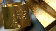 A padlock with a carved of Eiffel tower and Paris video