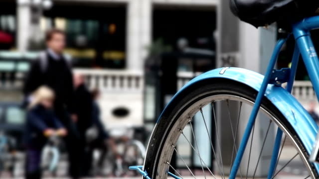 Padlocked city bicycle, pedestrians walking past. video
