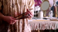 Paint covered hands of an artist in smock holding paintbrushes video